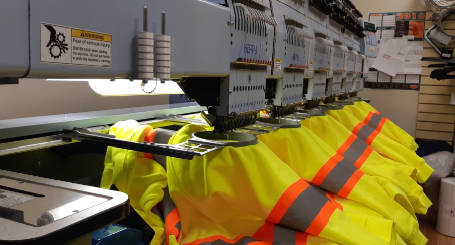 embroidery machines decorating yellow work jackets
