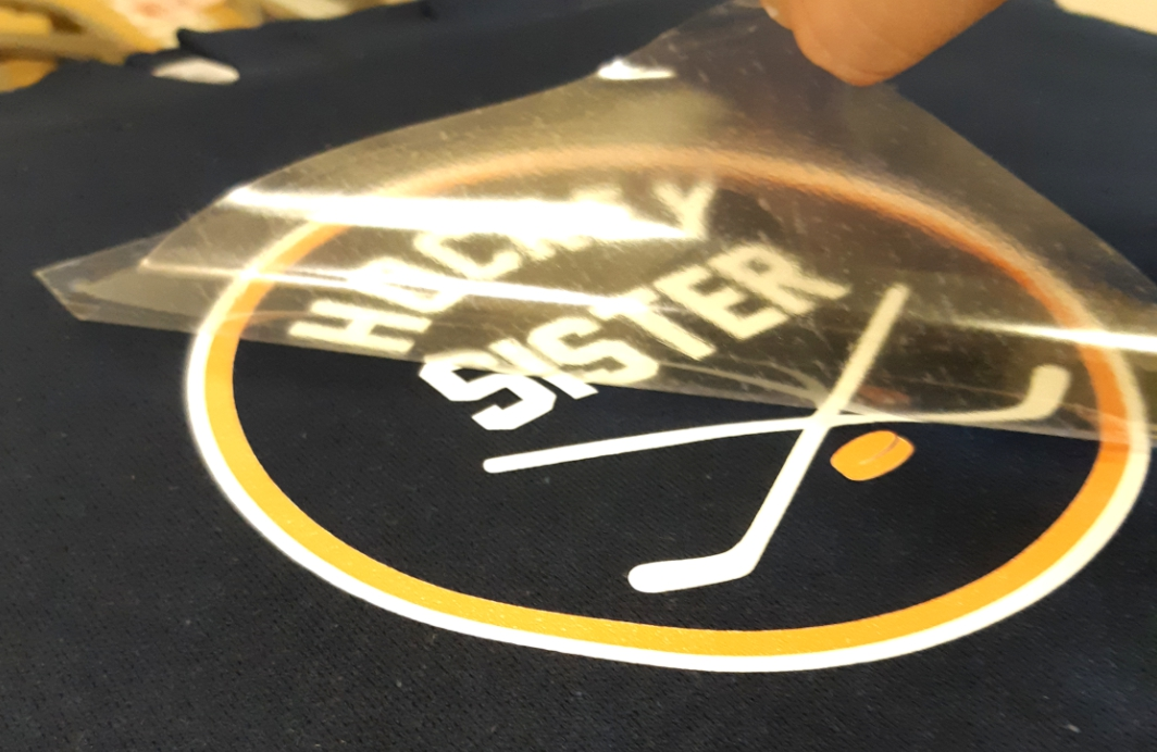 digital logo being heat applied to black t shirt